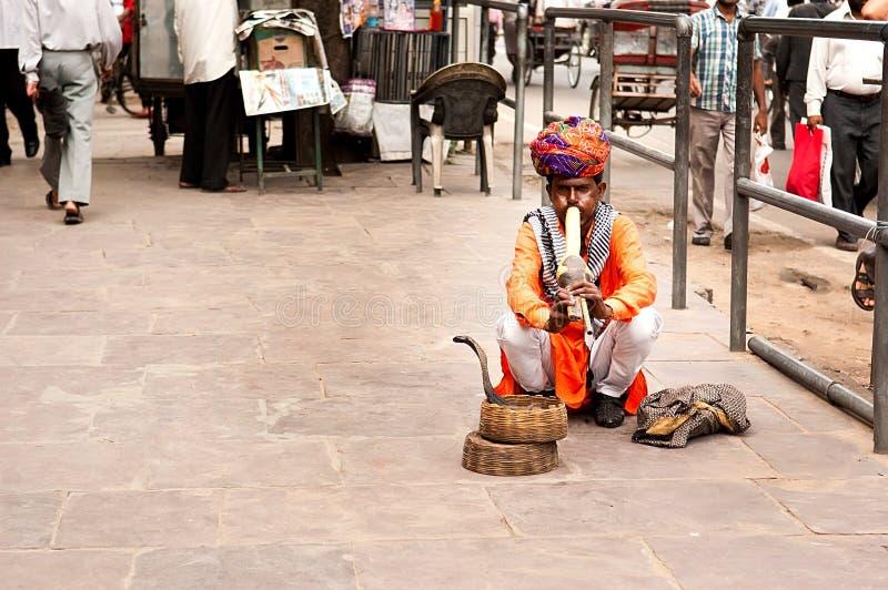 Ein Schlangenbeschwörer spielt die Flöte für die Kobra, die auf der Straße nahe Fort-Bernstein im Dezember sitzt stockbild