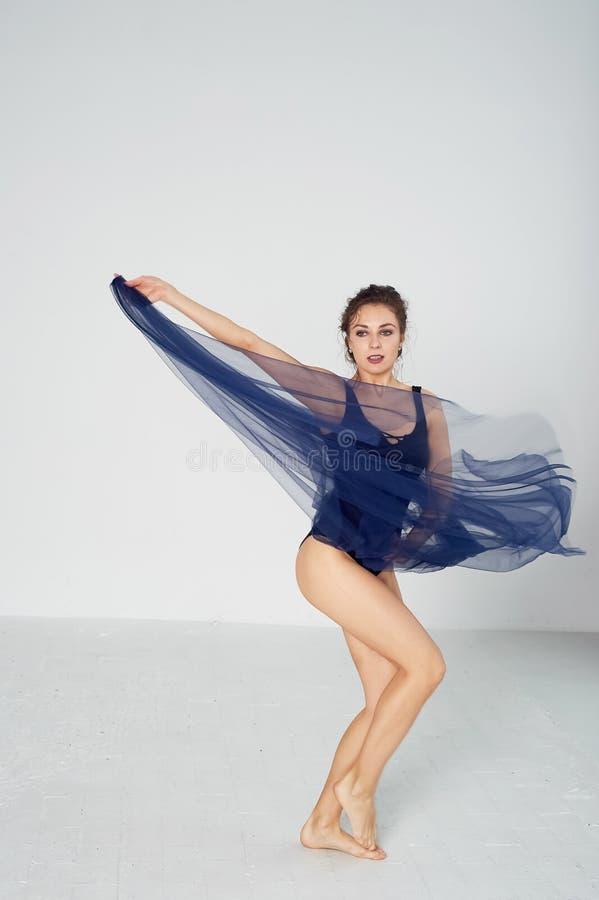 Ein schlanker Turner in den schwarzen Strumpfhosent?nzen mit einem Blau Chiffon-, das sich entwickelt ?sthetik des Tanzes lizenzfreies stockbild