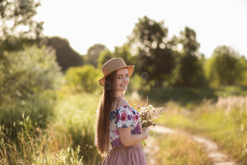 Ein schlankes Mädchen in einem Strohhut und mit einer Strohhandtasche, die einen Blumenstrauß von Gänseblümchen in der Wiese hält lizenzfreie stockbilder