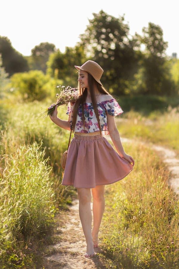 Ein schlankes Mädchen in einem Strohhut und mit einer Strohhandtasche, die einen Blumenstrauß von Gänseblümchen in der Wiese hält lizenzfreies stockbild