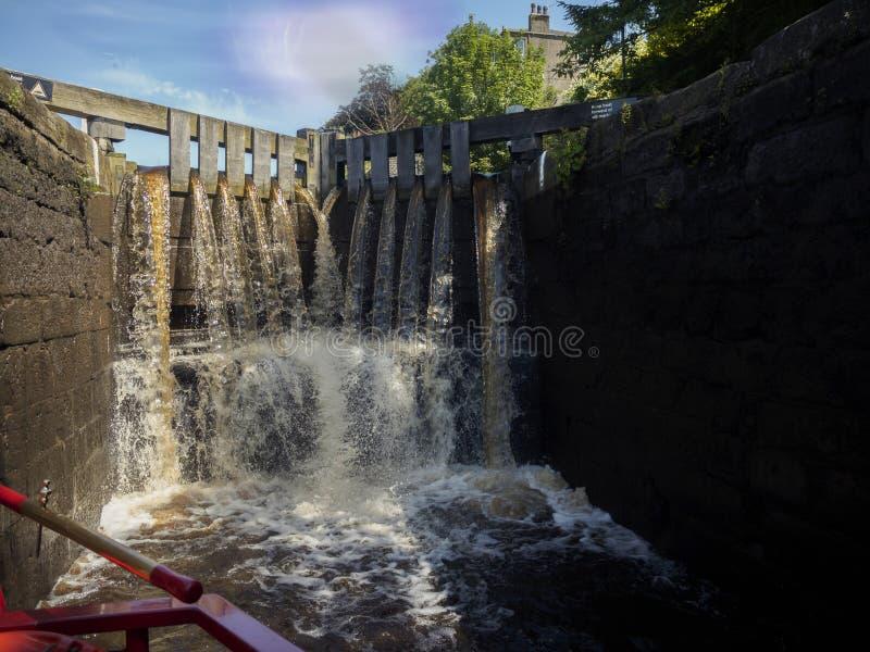 Ein schmales Boot in einem Kanalverschluß als dem Verschluss füllt mit Wasser lizenzfreies stockfoto