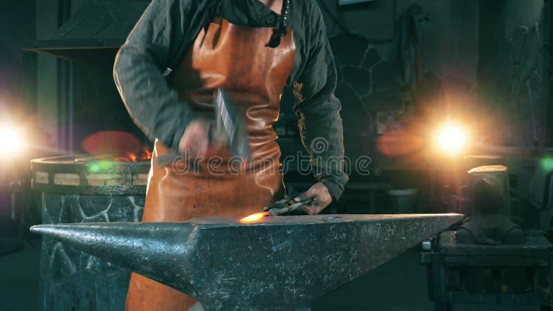 Ein Schmied hammert ein heißes Messer auf dem Bösen stock footage