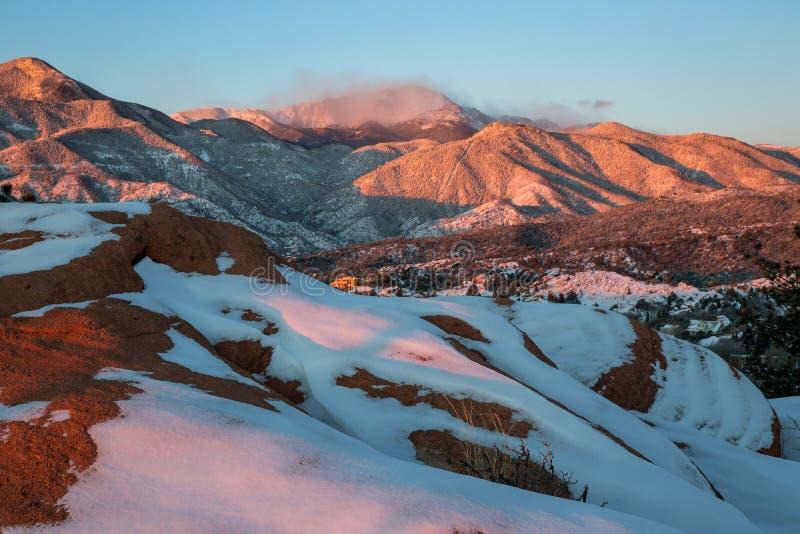 Ein schneebedeckter Sonnenaufgang im Garten der Götter mit Pikes Peak-Berg im Hintergrund stockbilder