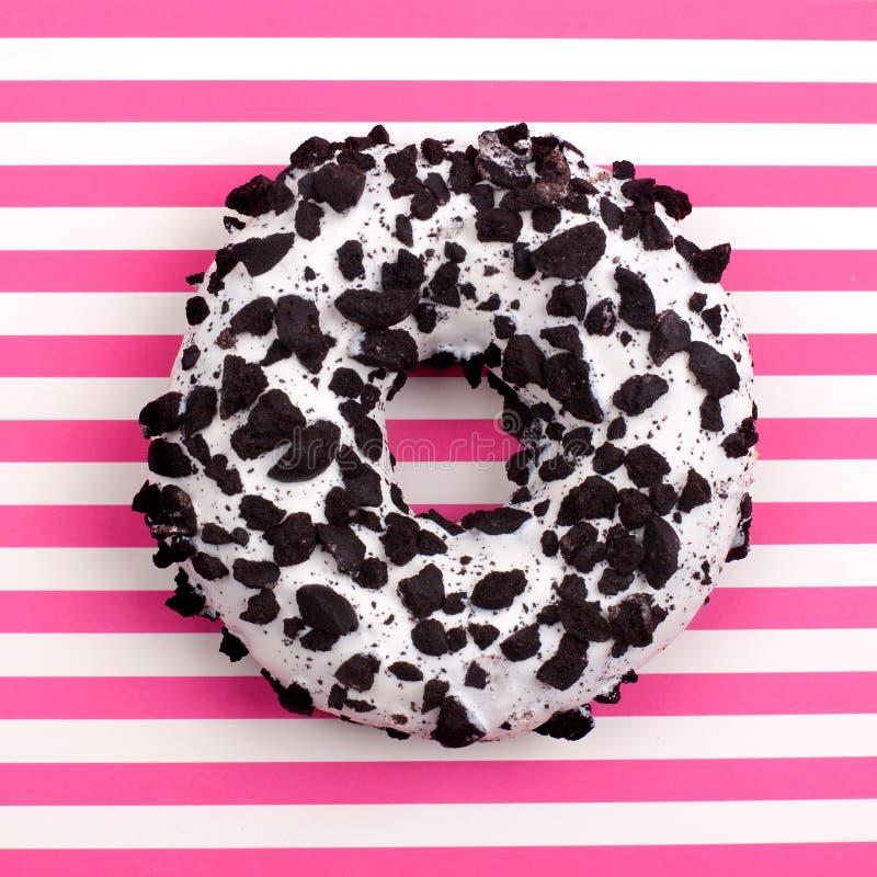 Ein Schokoladendonut auf gestreiftem Rosa- und weißemDraufsichtabschluß des Streifenhintergrundes oben stockfoto