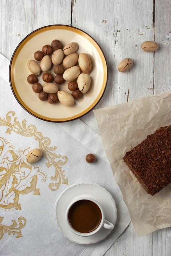 Ein Schokoladenkuchen, ein Tasse Kaffee und Nüsse auf dem weißen backgrou stockbild
