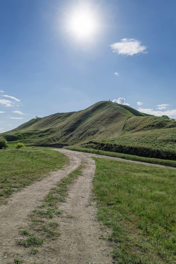 Ein Schotterweg, der zu einen Hügel führt lizenzfreie stockfotos