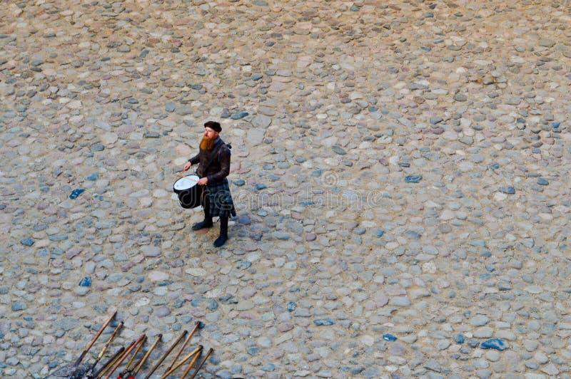 Ein schottischer Krieger, Soldat, Musiker schlägt die Trommel auf dem Quadrat eines mittelalterlichen alten Schlosses Nesvizh, We stockfotografie