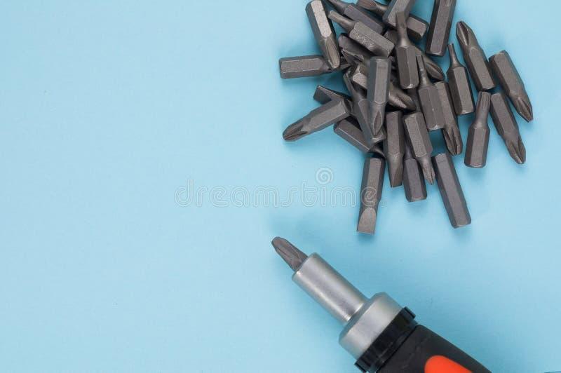 Ein Schraubenzieher mit Gummigriff der schwarzen und orange Farbe und Haufen von Metallstückchen stockfoto