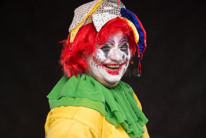Ein schrecklicher Clown mit einem schrecklichen Make-up und einem Hut lachend auf einem b lizenzfreie stockfotos