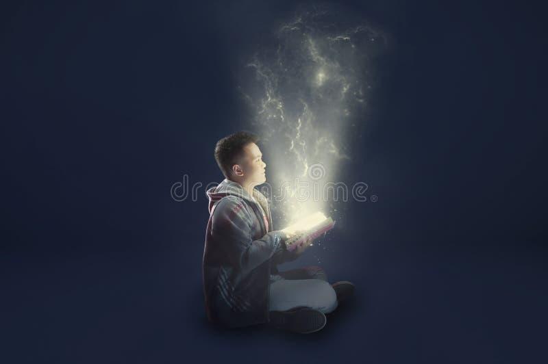 Ein Schuljunge, der eine Jackenholding und -lesung ein magisches Buch mit dem mystischen Licht herauskommt trägt Ideen von der Le lizenzfreies stockbild