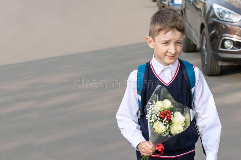 Ein Schuljunge mit einem Blumenstrauß von weißen Rosen in seinem Hand im Freien stockbilder