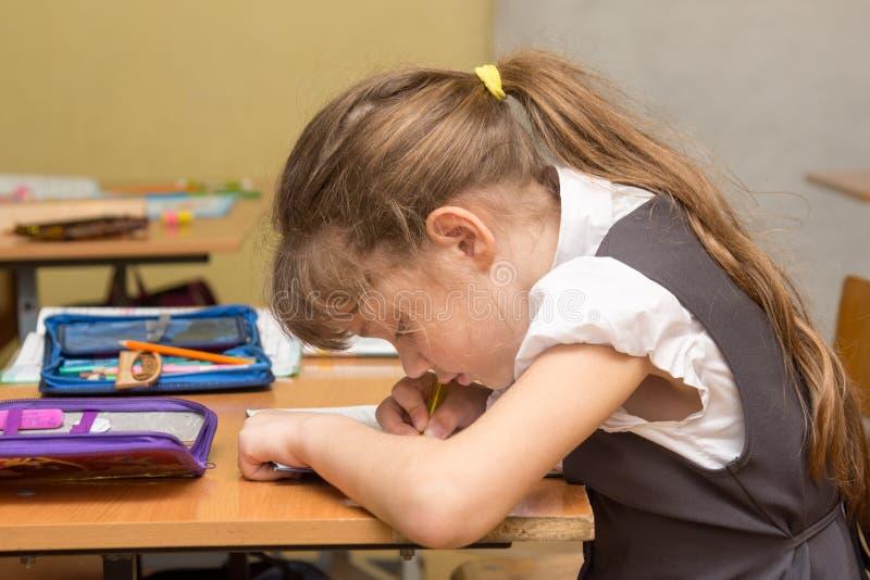 Ein Schulmädchen mit einer falschen Lage an der Lektion schreibt in ein Notizbuch stockbilder