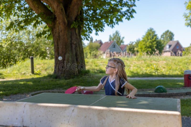 Ein Schulmädchen spielt Tischtennis Sie wird auf das Schlagen des b gerichtet stockbild