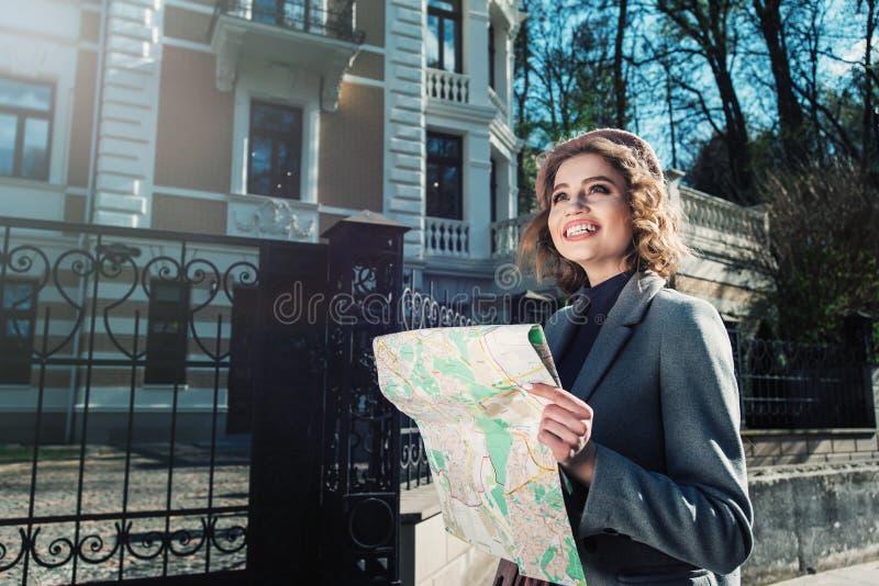 Ein Schuss einer netten jungen schönen gelockten lächelnden reisenden Frau des Kaukasiers, die eine Karte liest Frühlingssonnensc stockfoto
