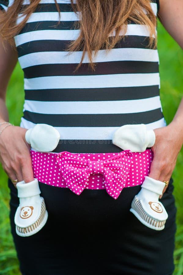 Ein schwangeres Mädchen in einem Kleid, auf einen Jungen wartend, Hände auf einem schwangeren Bauch und warten auf dieses, Unters lizenzfreies stockbild