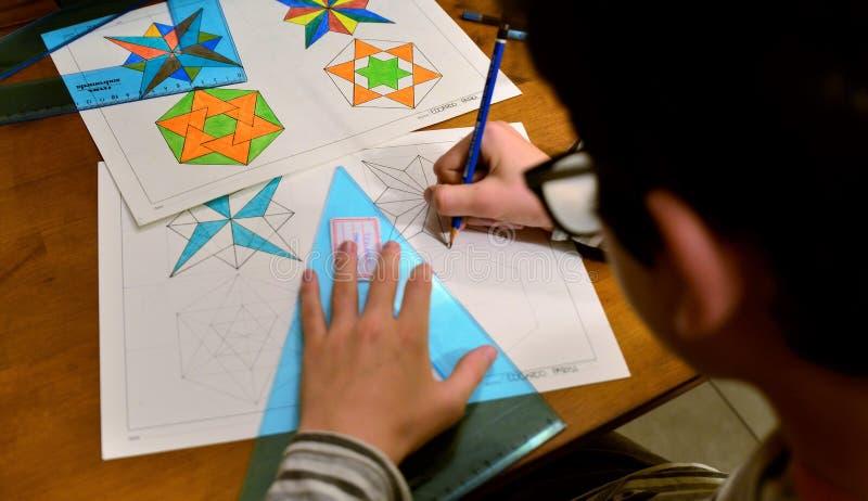 Ein schwarz-haariger kaukasischer Junge mit Gläsern tut seine technische zeichnende Hausarbeit lizenzfreie stockfotos