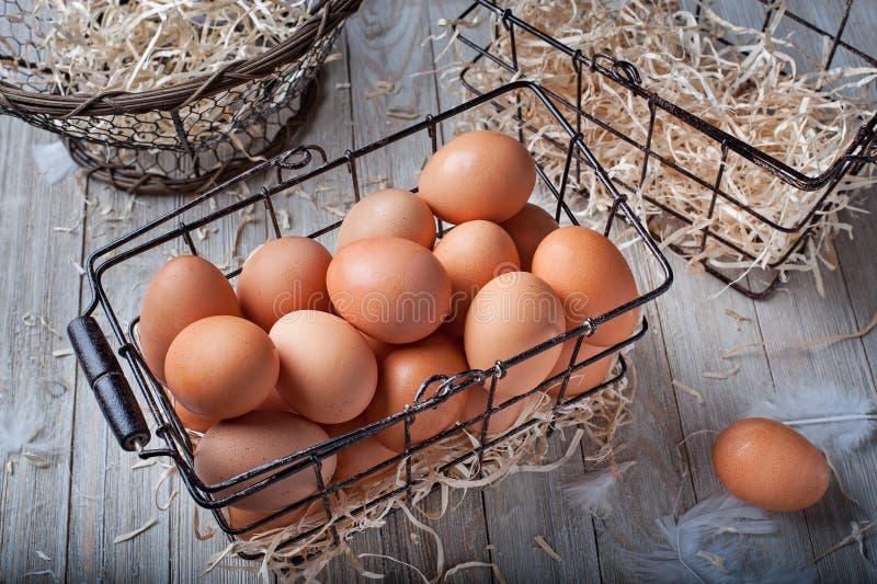 Ein schwarzer Drahtkorb füllte mit braunen Eiern und zwei leeren Körben lizenzfreies stockfoto