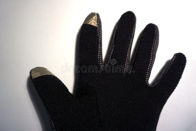 Ein schwarzer Handschuh auf einem weißen Hintergrund lizenzfreie stockfotografie