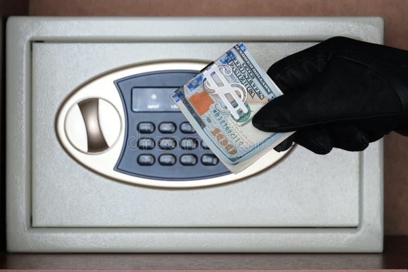 Ein schwarzer Handschuh hält ein Pack von amerikanischen Dollar vor einem Safe mit einem Kombinationsschloß Das Konzept des sch stockbild