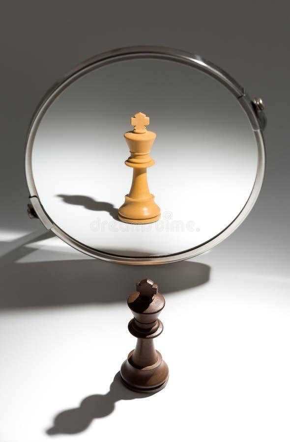 Ein schwarzer König schaut in einem Spiegel, um sich als weißer König zu sehen lizenzfreie stockbilder