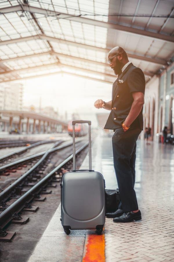 Ein schwarzer Kerl mit einer Tasche auf einer Plattform stockfoto
