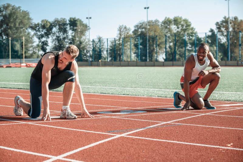 Ein schwarzer Läufer und ein weißer Mann haben Spaß am Anfang lizenzfreies stockfoto