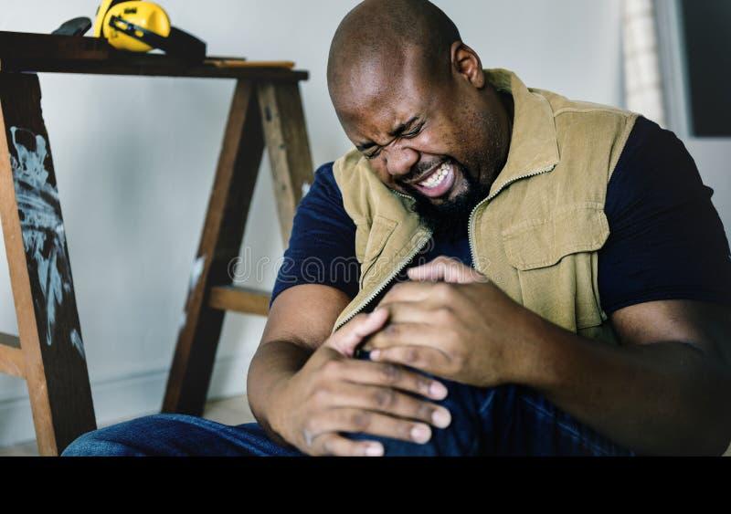 Ein schwarzer Mann, der in einem Haus verletzt erhält stockfotos