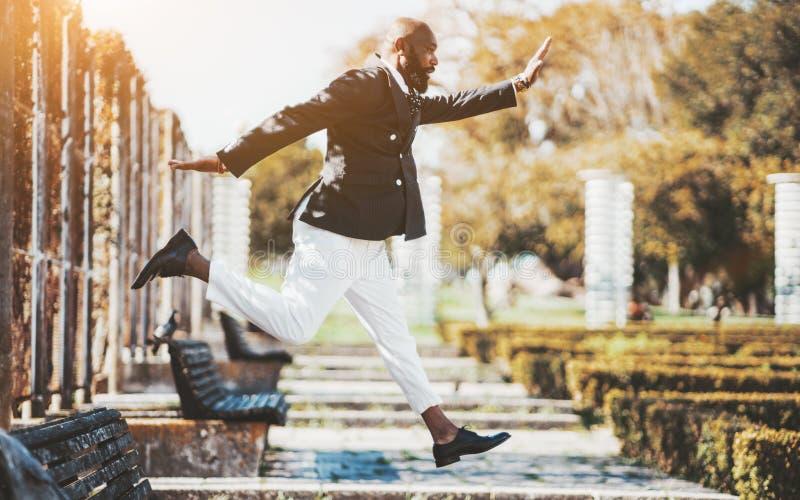 Ein schwarzer Mann springt in den Park stockfotos