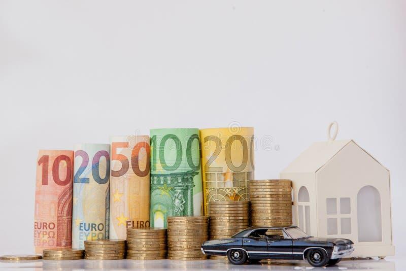 Ein schwarzes Modell eines Autos, des Hauses und zehn, zwanzig, fünfzig, hundert, zweihundert und des Münzeneuros rollte Rechnung lizenzfreie stockfotografie