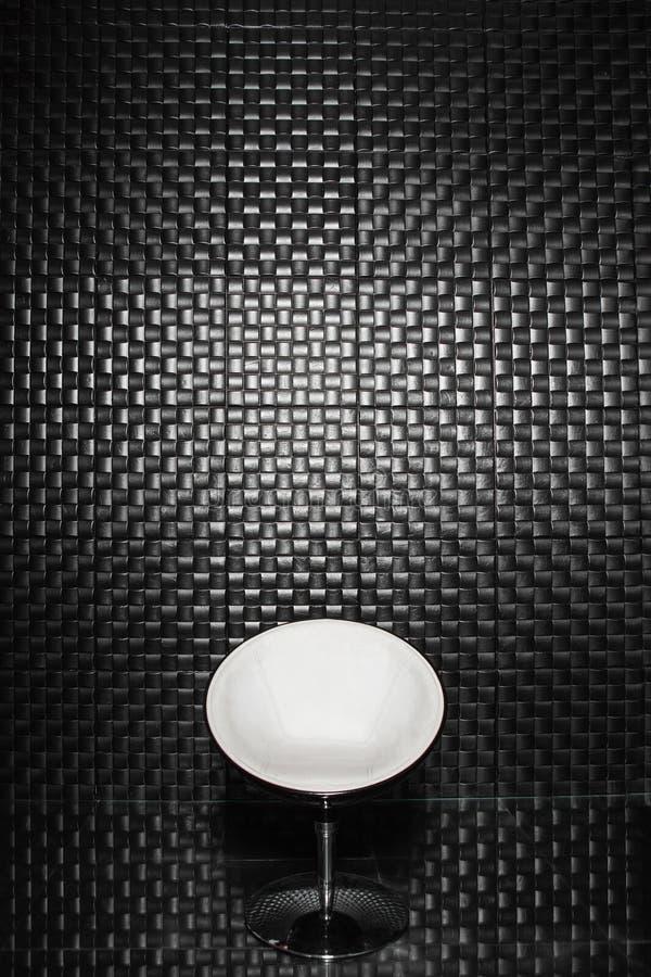 Ein Schwarzweiss-Stuhl gegen eine schwarze Wand lizenzfreies stockbild