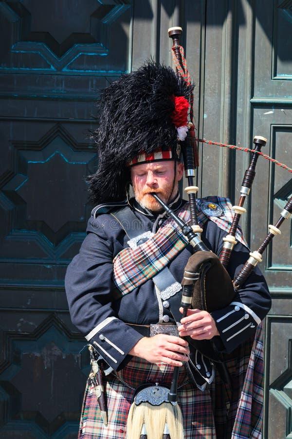 Ein Scotsman, der die traditionelle schottische Ausstattung spielt die Dudelsäcke trägt lizenzfreie stockfotografie