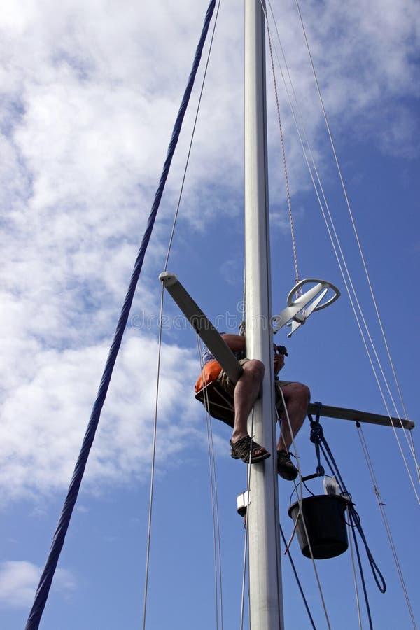Ein Seemann, der einen Mast repariert stockbilder