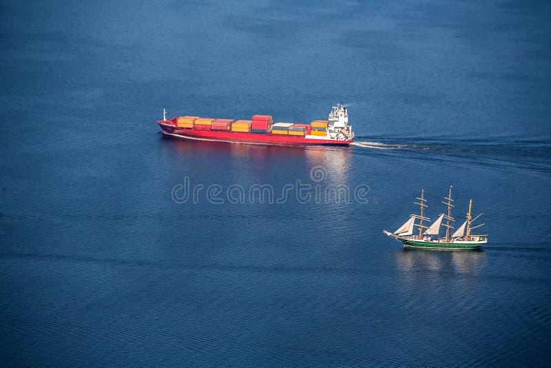 Ein Seeschiff ist- ein Containerschiff und ein Großsegler mit voller Geschwindigkeit in der hohen See Ansicht von oben n lizenzfreies stockfoto