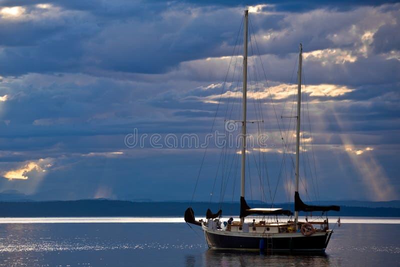 Ein Segelboot auf einem ruhigen See an der Dämmerung lizenzfreies stockfoto