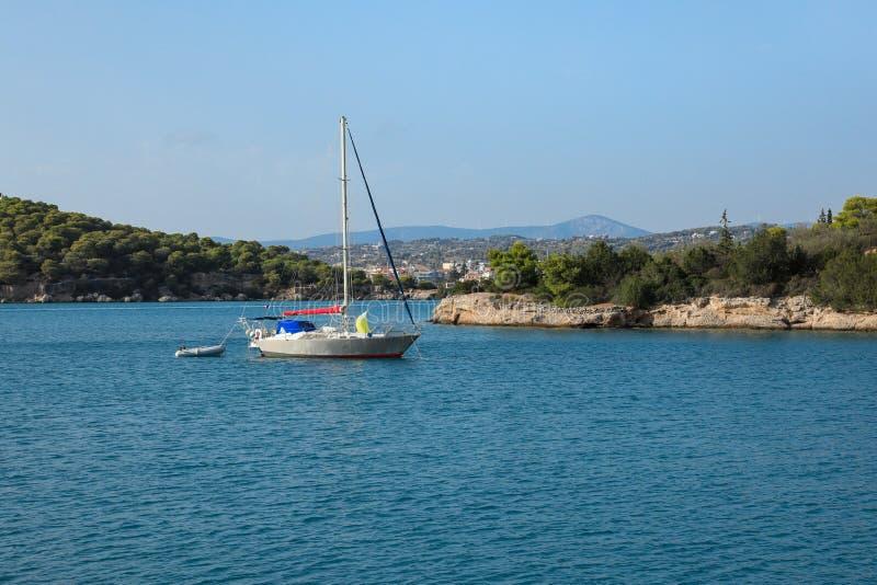 Ein Segelboot, das in einer Bucht nahe Porto Heli, Peloponnes, Griechenland verankert lizenzfreie stockfotografie