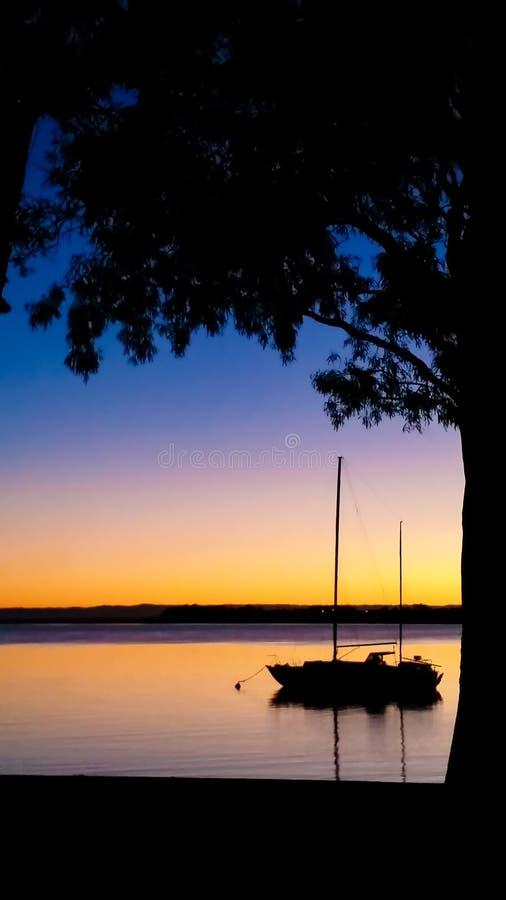 Ein Segelboot machte bei dem Sonnenuntergang fest, der durch Rahmen eines Baumschattenbildes gegen einen bunten Himmel - Raum für stockbilder