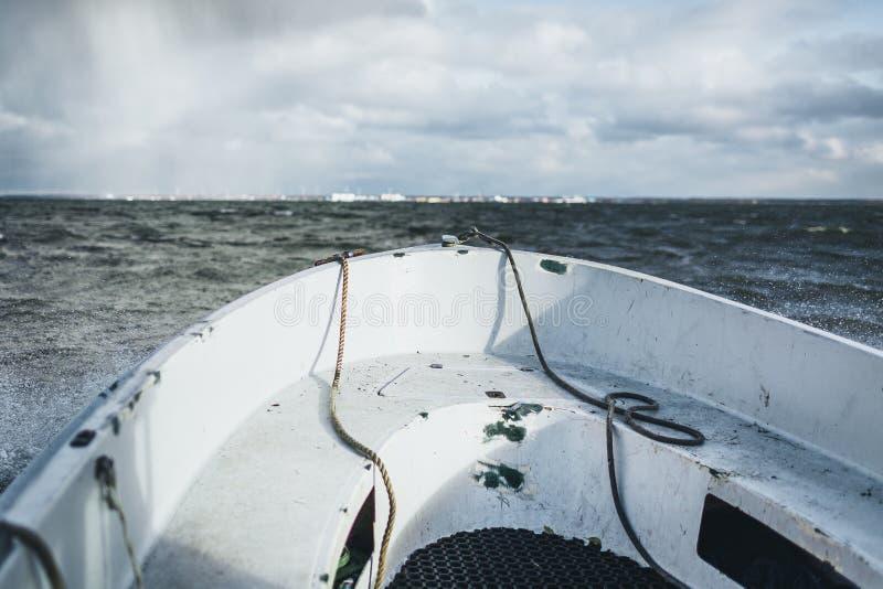 Ein Segeln des kleinen Bootes in Ostsee mit Paldiski, Estland-Hafen im Hintergrund stockbilder