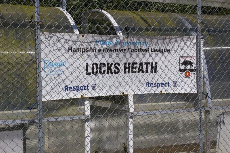 Ein Segeltuchzeichen, das ein lokales Fußballteam und -respekt innerhalb des Sports fördern und Satz hinter einem Drahtgewebezaun lizenzfreies stockfoto