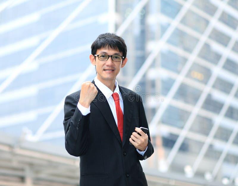 Ein sehr glücklicher Energiegeschäftsmann mit seinen Armen angehoben stockfoto