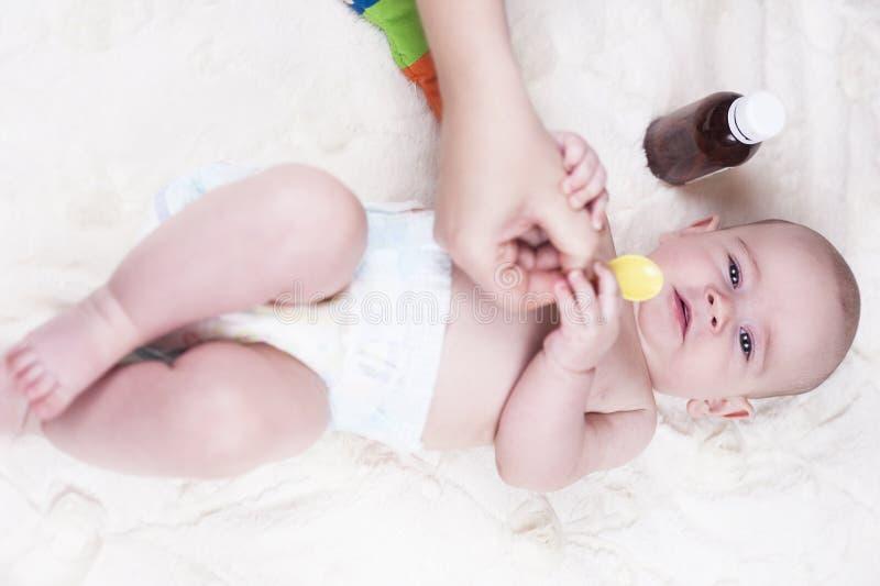 Ein sehr kleines Kind, ein Baby, liegt zurück in der Arztpraxis und der Doktor hört auf die Lungen stockbild
