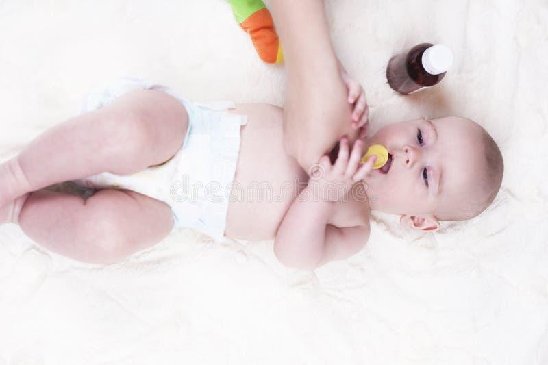 Ein sehr kleines Kind, ein Baby, liegt zurück in der Arztpraxis und der Doktor hört auf die Lungen lizenzfreies stockfoto