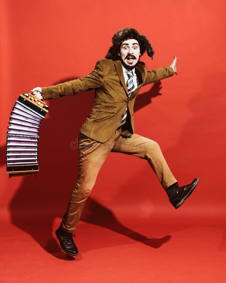 Ein sehr positiver Mann mit einem Akkordeon, das im Studio aufwirft stockfoto