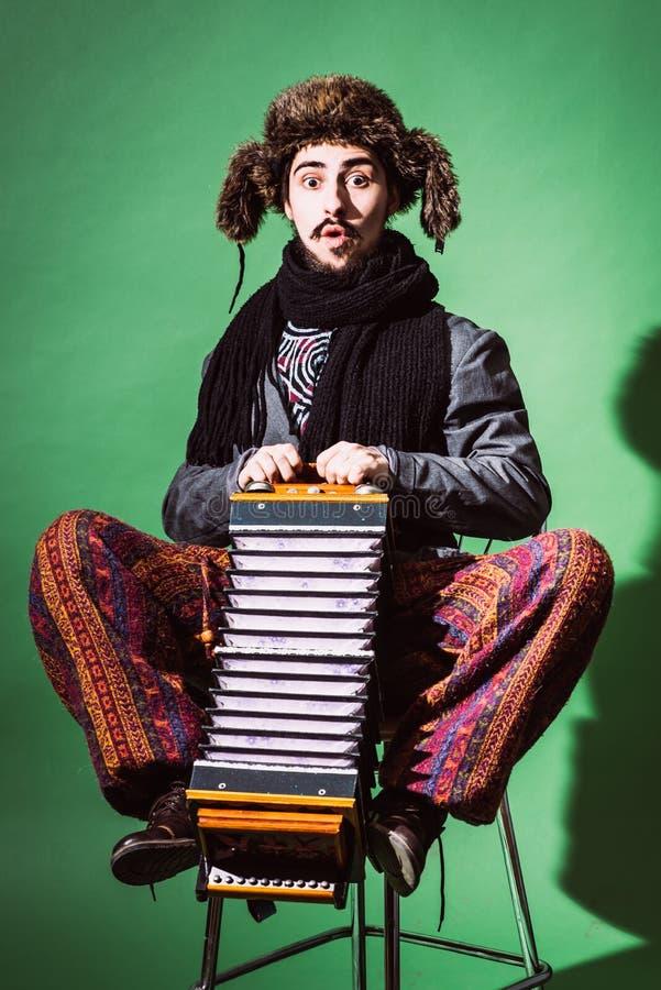 Ein sehr positiver Mann mit einem Akkordeon, das im Studio aufwirft stockfotografie