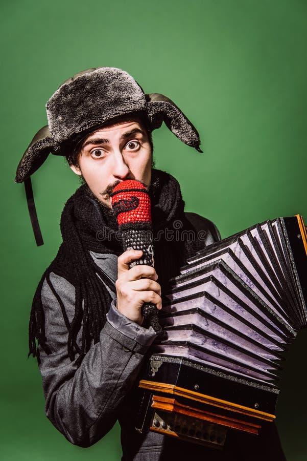 Ein sehr positiver Mann mit einem Akkordeon, das im Studio aufwirft lizenzfreie stockfotos