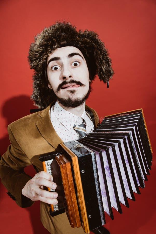 Ein sehr positiver Mann mit einem Akkordeon, das im Studio aufwirft lizenzfreies stockfoto