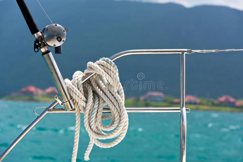 Ein Seil gebunden um eine Rettungsleine und eine Angelrute auf einer Yacht lizenzfreie stockfotografie