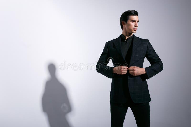 Ein Seitenbild des eleganten Geschäftsmannes im schwarzen Anzug, arranjens seine Jacke, schaut seitlich, lokalisiert auf einem Hi stockfoto