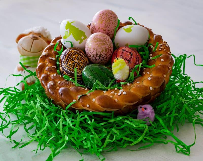Ein selbst gemachtes und geflochtenes Ostern-Nest machte vom Hefeteig mit bunten Ostereiern und kleinen Küken stockfoto