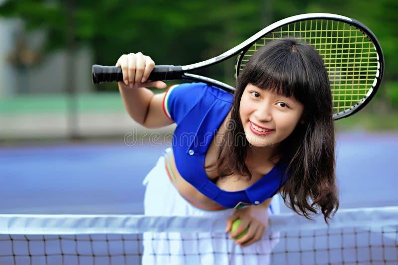 Ein sexy asiatisches Mädchen, das Tennis spielt stockfoto