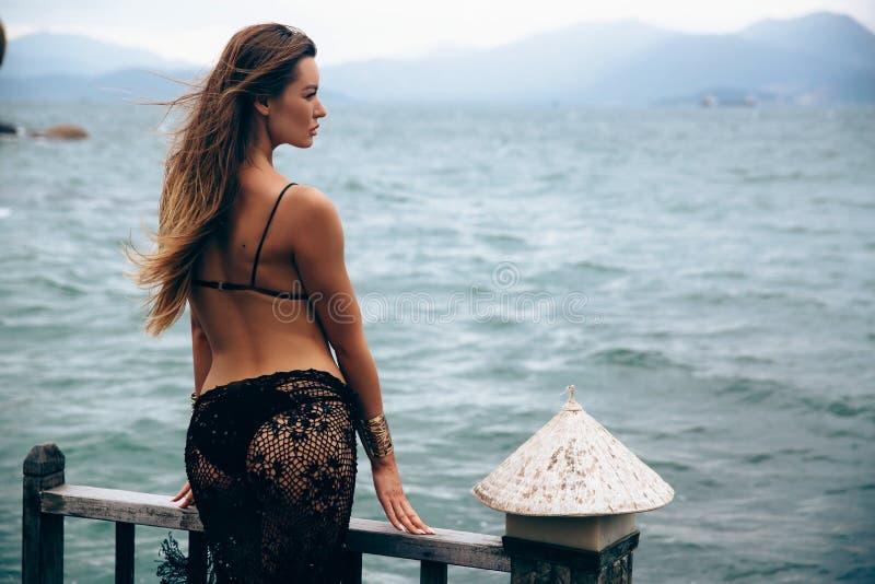 Ein sexy dunkelhaariges Mädchen der Nahaufnahme des europäischen Auftrittes steht allein auf dem Pier, betrachtet die nähernde Rü stockfotos
